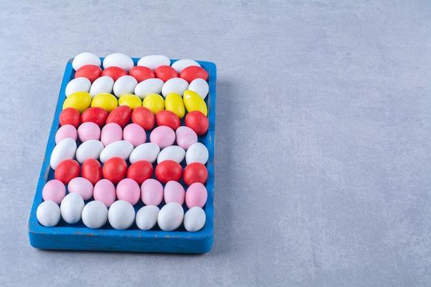 Ein blaues holzbrett mit bunten süßen jelly bean bonbons. foto in hoher qualität