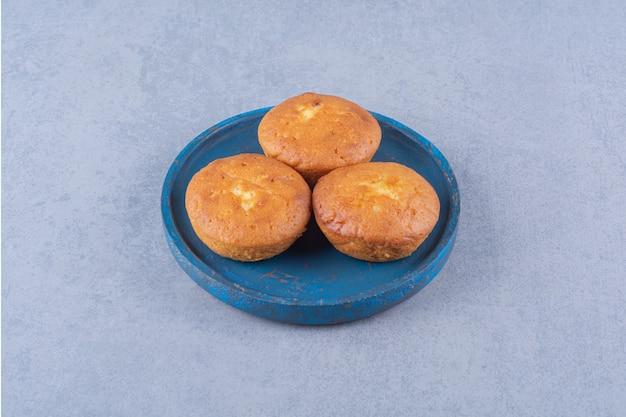 Ein blaues holzbrett mit drei süßen frischen cupcakes.