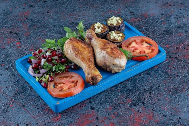 Ein blaues holzbrett mit gegrilltem hühnerfleisch