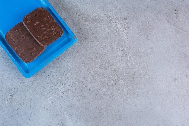 Ein blaues holzbrett mit schokoladenkeksen auf grau