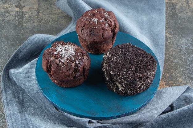 Ein blaues holzbrett mit schokoladenkuchen