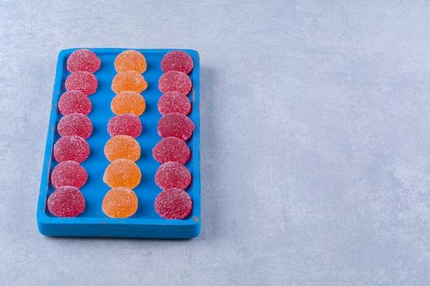 Ein blaues holzbrett voller roter und oranger zuckermarmeladen