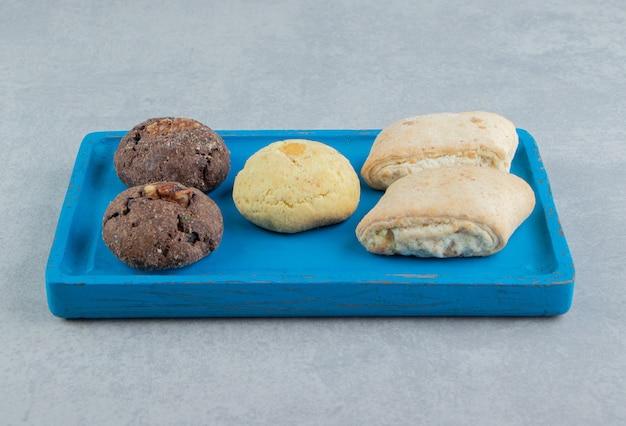 Ein blaues holzbrett voller süßer kekse. Kostenlose Fotos