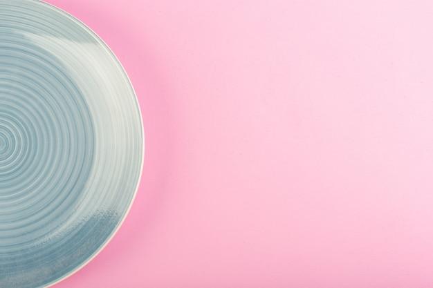 Ein blaues leeres tellerglas der draufsicht machte teller für mahlzeit auf rosa
