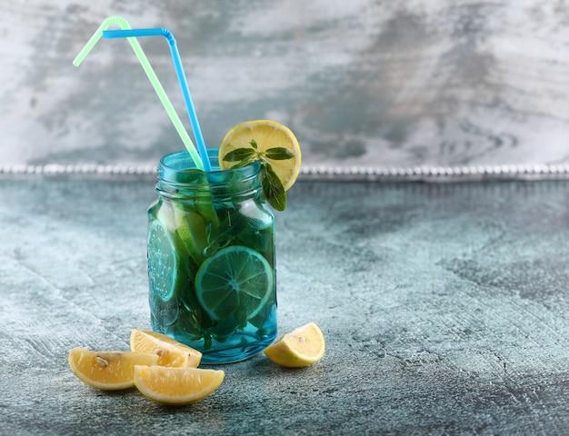 Ein blaues mojito glas mit zitrone und minze auf glänzendem hintergrund.
