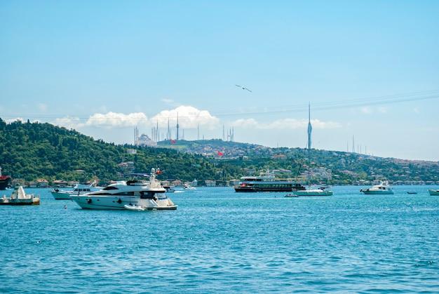 Ein blick auf die türkische natur, die boote und den bosporus von einem damm im istanbuler stadtteil arnavutky. türkisches san francisco. eine moschee in der ferne.