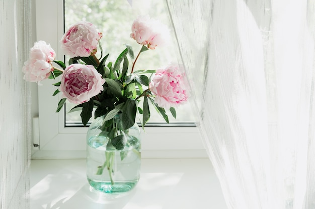 Ein blick auf einen strauß rosa pfingstrosen, die in einer vase am fenster stehen. konzept hintergrund, blumen, urlaub.