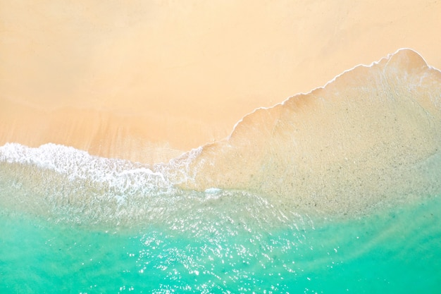 Ein blick aus der höhe eines tropischen strandes und der wellen, die an einem tropischen goldenen sandstrand brechen. die meereswellen winden sich sanft am schönen sandstrand entlang.