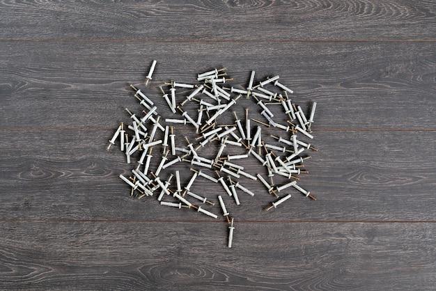 Ein blick von oben auf den haufen metall-stahl-schrauben oder dübel mit plastikkappen, die auf dem tisch isoliert sind?