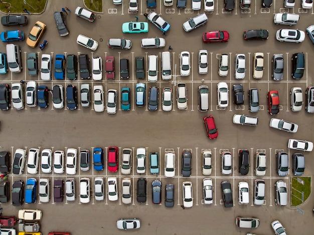 Ein blick von oben auf die schlangen der geparkten autos. starker verkehr auf dem parkplatz. suche nach plätzen auf dem belebten parkplatz. cruising für das parken im wohnheimbereich. schwierigkeiten beim parken in der stadt.