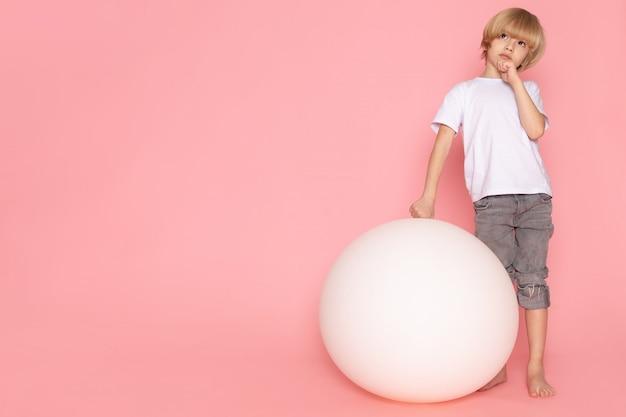 Ein blonder denkender junge der vorderansicht im weißen t-shirt, das mit weißem ball auf dem rosa schreibtisch liegt