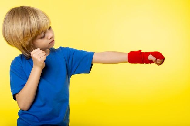 Ein blonder junge der vorderansicht, der das boxen im blauen t-shirt auf der gelben wand aufwirft