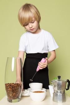 Ein blonder junge der vorderansicht, der kaffeegetränk auf dem tisch auf dem steinfarbenen raum vorbereitet