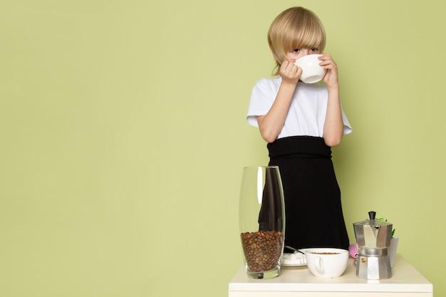 Ein blonder junge der vorderansicht im weißen t-shirt, das kaffee auf dem steinfarbenen raum trinkt