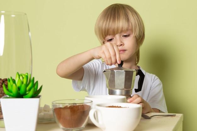 Ein blonder junge der vorderansicht im weißen t-shirt, das kaffee auf der steinfarbenen wand vorbereitet