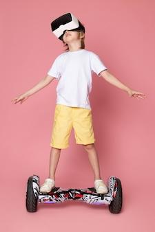Ein blonder junge der vorderansicht im weißen t-shirt, das vr auf segway auf dem rosa raum spielt