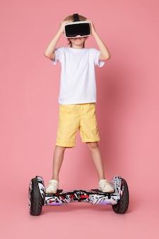 Ein blonder junge der vorderansicht im weißen t-shirt, das vr reitet segway auf dem rosa raum spielt
