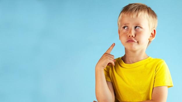 Ein blonder junge in einem gelben t-shirt schaut nachdenklich auf eine blaue oberfläche