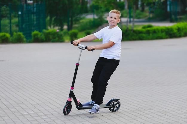 Ein blonder junge in einem weißen t-shirt und einer schwarzen hose, der einen roller fährt. foto in hoher qualität