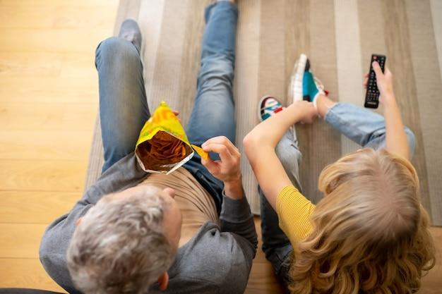 Ein blonder teenie sitzt mit ihrem vater auf dem boden und isst chips