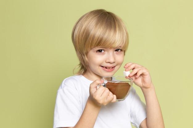 Ein blondes lächelndes kind der vorderansicht im weißen t-shirt, das kaffeepulver auf dem steinfarbenen schreibtisch hält