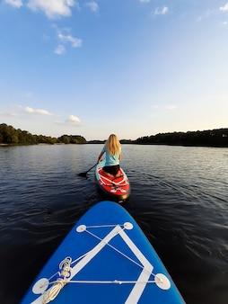 Ein blondes mädchen auf den knien schwimmt auf einem sup-paddleboard und bedient sich mit einem ruder. das zweite brett schwebt dahinter. rückansicht