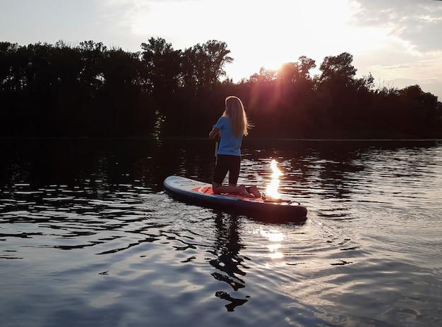 Ein blondes mädchen auf den knien schwimmt auf einem sup-paddleboard vor dem hintergrund eines abendlichen sees oder flusses. rückansicht