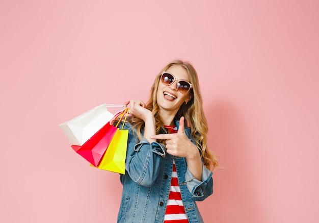 Ein blondes mädchen, das mit dem einkaufen glücklich ist, das sie getan hat und geste über rosafarbenem hintergrund zeigt