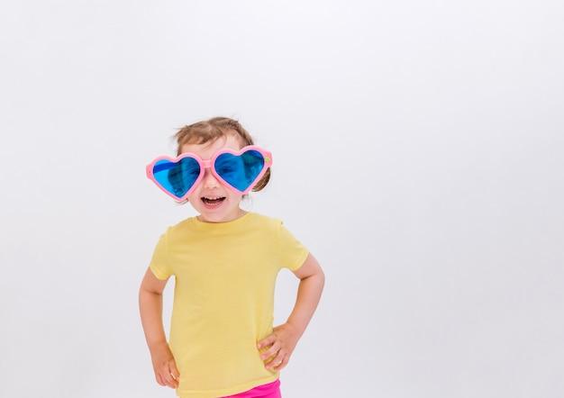 Ein blondes mädchen in der großen lustigen brille lächelt, die auf einem weißen raum steht. tag des lachens.