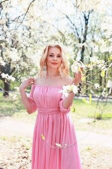 Ein blondes mädchen in einem rosa kleid nahe einem magnolienbaum.