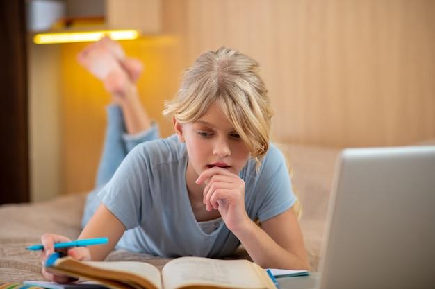 Ein blondes mädchen liegt auf dem bett und macht ihren unterricht