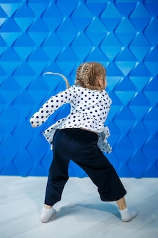 Ein blondes mädchen von 7 jahren in einer jacke mit erbsen auf blauem hintergrund tanzt und lacht, helle kindergefühle der freude, eine glückliche kindheit