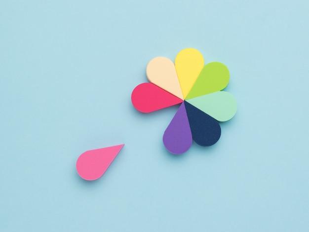 Ein blütenblatt, das sich von einer bunten schwammblume auf einer blauen oberfläche trennt