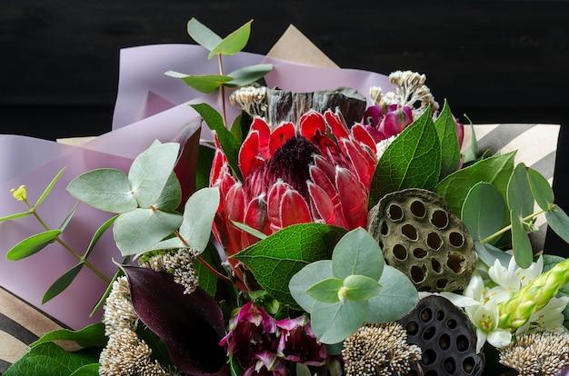 Ein blumenstrauß auf einem dunklen hölzernen hintergrund. strauß mit protea, orchidee, mohn, sukkulente ..