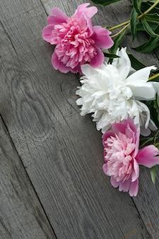 Ein blumenstrauß aus rosa und weiß blühenden pfingstrosenblüten auf der oberfläche der alten bretter mit textur.