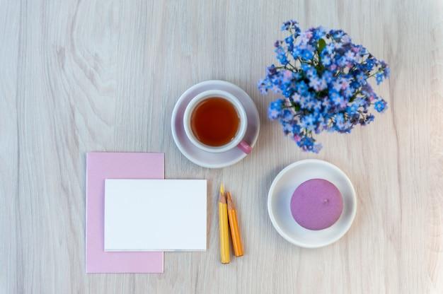 Ein blumenstrauß aus vergissmeinnicht-blumen auf einem tisch mit einer tasse tee und einer karte als glückwunschtext. urlaubshintergrund, kopierraum, weichzeichner, draufsicht.