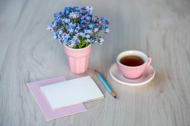 Ein blumenstrauß aus vergissmeinnicht-blumen auf einem tisch mit einer tasse tee und einer karte als glückwunschtext. urlaubshintergrund, kopierraum, weichzeichner.