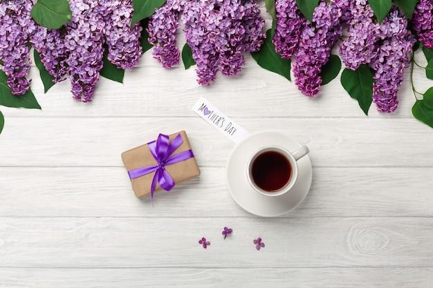 Ein blumenstrauß flieder mit tasse tee, geschenkbox und liebesanmerkung auf weißen brettern. muttertag