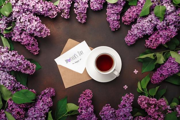 Ein blumenstrauß flieder mit tasse tee, handwerksumschlag, liebesanmerkung über rostigen hintergrund. muttertag