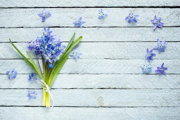 Ein blumenstrauß von blauen blumen auf einem hölzernen hintergrund