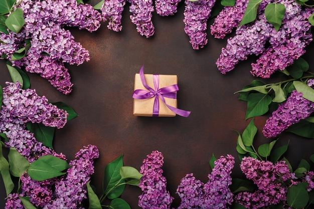 Ein blumenstrauß von fliedern mit geschenkbox auf rostigem hintergrund. muttertag