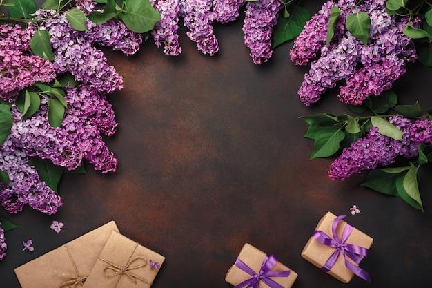 Ein blumenstrauß von fliedern mit geschenkbox, handwerksumschlag auf rostigem hintergrund. muttertag