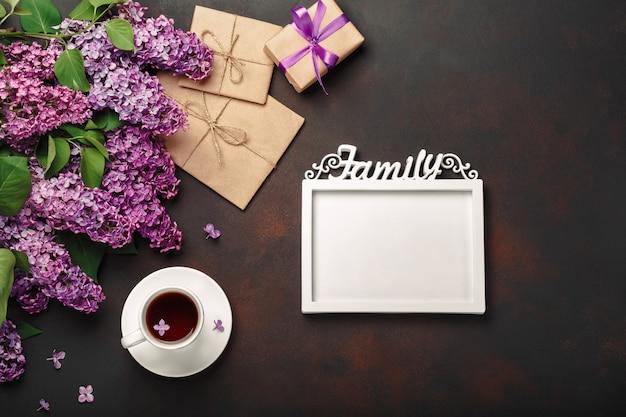 Ein blumenstrauß von fliedern mit tasse tee, ein weißer rahmen für aufschrift, geschenkbox, handwerksumschlag, eine liebesanmerkung über rostigen hintergrund