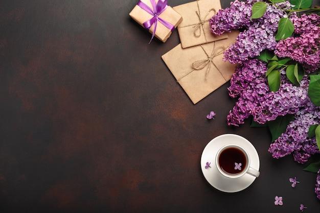 Ein blumenstrauß von fliedern mit tasse tee, geschenkbox, handwerksumschlag, eine liebesanmerkung über rostigen hintergrund. muttertag