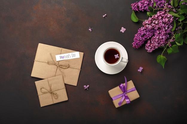 Ein blumenstrauß von fliedern mit tasse tee, geschenkbox, handwerksumschlag, liebesanmerkung über rostigen hintergrund. muttertag