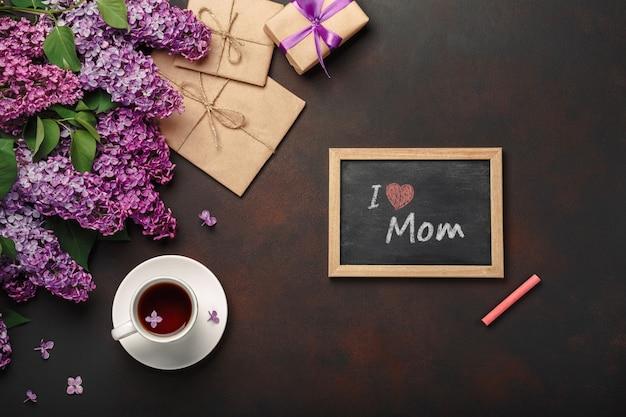 Ein blumenstrauß von fliedern mit tasse tee, kreidebrett, geschenkbox, handwerksumschlag, liebesanmerkung über rostigen hintergrund. muttertag