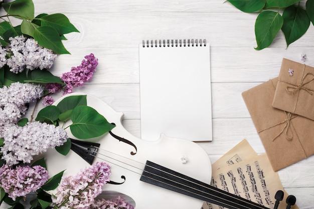 Ein blumenstrauß von fliedern mit violine, brief, notizblock und musikblatt auf einem weißen holztisch. top wiev mit platz für ihren text