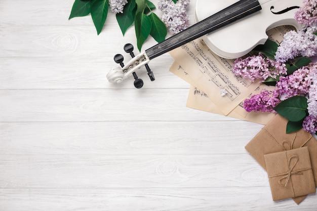 Ein blumenstrauß von fliedern mit violine, buchstaben und musikblatt auf einem weißen holztisch. top wiev mit platz für ihren text
