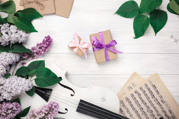 Ein blumenstrauß von fliedern mit violine, geschenkbox und musikblatt auf einem weißen holztisch. top wiev mit platz für ihren text