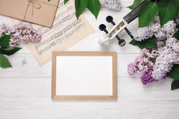 Ein blumenstrauß von fliedern mit violine, kreidebrett und musikblatt auf einem weißen holztisch. top wiev mit platz für ihren text